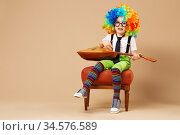Blithesome children. Happy clown boy in large neon colored wig playing the balalaika and singing. Стоковое фото, фотограф Nataliia Zhekova / Фотобанк Лори