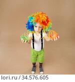 Little boy in clown wig plays with a spring. Стоковое фото, фотограф Nataliia Zhekova / Фотобанк Лори