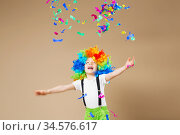 Happy clown boy with large colorful wig. Let's party! Funny kid clown. 1 April Fool's day concept. Portrait of a child throws up a multi-colored tinsel and confetti. Стоковое фото, фотограф Nataliia Zhekova / Фотобанк Лори