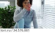 Woman having a coffee sitting on window sill. Стоковое видео, агентство Wavebreak Media / Фотобанк Лори