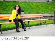 A beautiful girl is sitting on a park bench on a background of green... Стоковое фото, фотограф Zoonar.com/Figurniy Sergey / age Fotostock / Фотобанк Лори