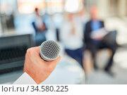 Redner oder Speaker mit der Hand am Mikrofon bei einem Referat oder... Стоковое фото, фотограф Zoonar.com/Robert Kneschke / age Fotostock / Фотобанк Лори