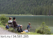 Couple et enfants au bord du Lac de Dobbiaco, Region du Trentin-Haut... Редакционное фото, фотограф Christian Goupi / age Fotostock / Фотобанк Лори
