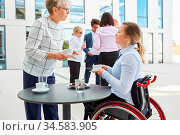 Inklusion unter Geschäftsleuten mit Frau im Rollstuhl beim Smalltalk... Стоковое фото, фотограф Zoonar.com/Robert Kneschke / age Fotostock / Фотобанк Лори