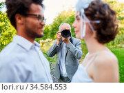 Hochzeitsfotograf fotografiert Brautpaar am Hochzeitstag in der Natur. Стоковое фото, фотограф Zoonar.com/Robert Kneschke / age Fotostock / Фотобанк Лори