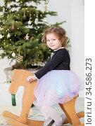 Portrait of a cute little girl. Little girl among Christmas decorations. Girl riding a rocking deer. Стоковое фото, фотограф Nataliia Zhekova / Фотобанк Лори
