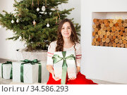 Happy young woman with Christmas gifts. Girl delighted with gift. Стоковое фото, фотограф Nataliia Zhekova / Фотобанк Лори