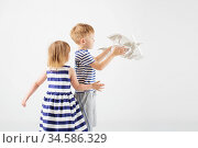 Little Children playing with paper toy airplane against a white background. Стоковое фото, фотограф Nataliia Zhekova / Фотобанк Лори