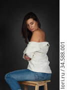 Beautiful sporty lady in white blazer and blue denim jeans against dark background. Стоковое фото, фотограф Nataliia Zhekova / Фотобанк Лори