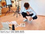 Fotograf betrachtet Fotos für Bildauswahl auf dem Fußboden im Fotostudio. Стоковое фото, фотограф Zoonar.com/Robert Kneschke / age Fotostock / Фотобанк Лори