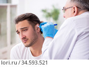 Young man visiting experienced doctor otolaryngologist. Стоковое фото, фотограф Elnur / Фотобанк Лори