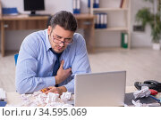 Sick male employee suffering at workplace. Стоковое фото, фотограф Elnur / Фотобанк Лори