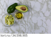 View of two avocados, olive oil bottle and cut avocado in a bowl on white pattern table background. Стоковое фото, агентство Wavebreak Media / Фотобанк Лори