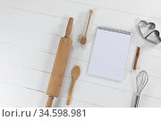 View of a composition of a notebook with cookie cutters, whisker and rolling pin on white surface. Стоковое фото, агентство Wavebreak Media / Фотобанк Лори