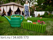 Watering can in the garden, gardener on background. Стоковое фото, фотограф Tryapitsyn Sergiy / Фотобанк Лори