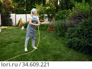 Woman with hose watering flowers in the garden. Стоковое фото, фотограф Tryapitsyn Sergiy / Фотобанк Лори