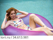 A smiling 27 year old redhead woman in a swimming pool resting on... Стоковое фото, фотограф Joseph De Sciose / age Fotostock / Фотобанк Лори