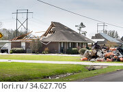 Lake Charles, Louisiana. USA - September 6, 2020:  Hurricane Laura. The destruction of the roof of a new house by a strong wind and a mountain of debris near the road. Редакционное фото, фотограф Ирина Кожемякина / Фотобанк Лори