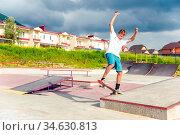 Boy skateboarder in a skate park doing an ollie trick on a skateboard... Стоковое фото, фотограф Zoonar.com/Ian Iankovskii / easy Fotostock / Фотобанк Лори