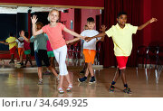 Smiling children primary school trying dancing salsa dance in modern studio. Стоковое фото, фотограф Яков Филимонов / Фотобанк Лори
