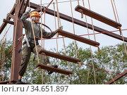 Preteen beautiful girl climbs on rope harness in summer wood park. Стоковое фото, фотограф Кекяляйнен Андрей / Фотобанк Лори