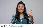 happy asian woman showing thumbs up over grey. Стоковое видео, видеограф Syda Productions / Фотобанк Лори