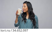 happy asian woman drinking coffee. Стоковое видео, видеограф Syda Productions / Фотобанк Лори