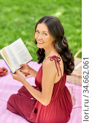 happy woman reading book at picnic in summer park. Стоковое фото, фотограф Syda Productions / Фотобанк Лори