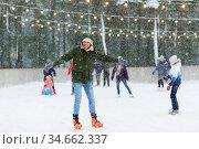 happy young man at outdoor skating rink in winter. Стоковое фото, фотограф Syda Productions / Фотобанк Лори