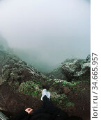 Man stand on cliff look at the fog. Стоковое фото, фотограф Zoonar.com/Oleksii Hrecheniuk / easy Fotostock / Фотобанк Лори