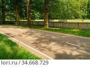 Gerade Landstraße vor Zaun mit Wiese im Sommer. Стоковое фото, фотограф Zoonar.com/Robert Kneschke / age Fotostock / Фотобанк Лори