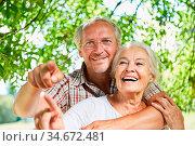 Glückliches Paar Senioren lacht zusammen in der Natur im Sommer in... Стоковое фото, фотограф Zoonar.com/Robert Kneschke / age Fotostock / Фотобанк Лори