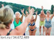 Gruppe Senior Frauen beim Rückentraining zusammen am See im Sommer. Стоковое фото, фотограф Zoonar.com/Robert Kneschke / age Fotostock / Фотобанк Лори