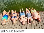 Gruppe Senioren entspannt beim Sonnenbaden auf einem Steg am Badesee... Стоковое фото, фотограф Zoonar.com/Robert Kneschke / age Fotostock / Фотобанк Лори