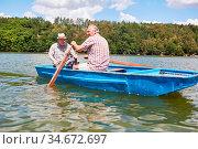 Senior Mann und sein Vater beim Rudern zusammen auf dem See im Sonnenschein. Стоковое фото, фотограф Zoonar.com/Robert Kneschke / age Fotostock / Фотобанк Лори