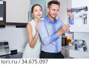 Young man and woman are choosing new mixer tap. Стоковое фото, фотограф Яков Филимонов / Фотобанк Лори