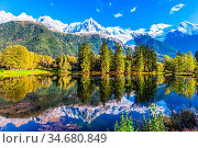 Snowy peaks of the Alps are beautifully reflected in the lake. Park... Стоковое фото, фотограф Zoonar.com/kavram / easy Fotostock / Фотобанк Лори