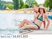 Junges fröhliches Paar auf einem Steg beim Plantschen im Wasser im... Стоковое фото, фотограф Zoonar.com/Robert Kneschke / age Fotostock / Фотобанк Лори