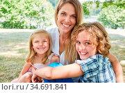 Mutter und ihre zwei Kinder lachen glücklich in die Kamera auf einer... Стоковое фото, фотограф Zoonar.com/Robert Kneschke / age Fotostock / Фотобанк Лори