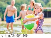 Kleines Mädchen spielt mit einem bunten Ball im Meer in den Sommerferien. Стоковое фото, фотограф Zoonar.com/Robert Kneschke / age Fotostock / Фотобанк Лори