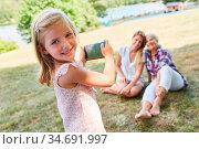 Kleines Mädchen fotografiert mit dem Smartphone ihre Mutter und ihre... Стоковое фото, фотограф Zoonar.com/Robert Kneschke / age Fotostock / Фотобанк Лори