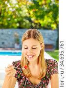Glückliche Frau isst Salat mit Gabel im Garten. Стоковое фото, фотограф Zoonar.com/Robert Kneschke / age Fotostock / Фотобанк Лори