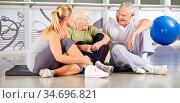 Gruppe Senioren sitzt auf dem Boden und macht eine Pause im Fitnesscenter. Стоковое фото, фотограф Zoonar.com/Robert Kneschke / age Fotostock / Фотобанк Лори