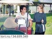Positive man and woman golfers riding golf cart. Стоковое фото, фотограф Яков Филимонов / Фотобанк Лори