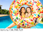 Two girls laughing inside inflatable doughnut. Стоковое фото, фотограф Сергей Новиков / Фотобанк Лори