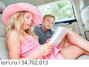 Mädchen auf dem Rücksitz im Auto liest ein spannendes Buch auf der... Стоковое фото, фотограф Zoonar.com/Robert Kneschke / age Fotostock / Фотобанк Лори