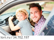 Kleiner Junge sitzt am Lenkrad im Auto und lernt fahren zusammen ... Стоковое фото, фотограф Zoonar.com/Robert Kneschke / age Fotostock / Фотобанк Лори