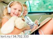 Mädchen mit Kuscheltier und Kopfhörer im Auto hört Musik oder ein... Стоковое фото, фотограф Zoonar.com/Robert Kneschke / age Fotostock / Фотобанк Лори