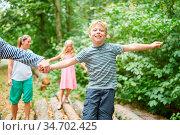 Kinder balancieren auf Baumstämmen auf einem Ausflug mit Hilfe ihre... Стоковое фото, фотограф Zoonar.com/Robert Kneschke / age Fotostock / Фотобанк Лори