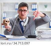 Businessman in the office smoking holding human skull. Стоковое фото, фотограф Elnur / Фотобанк Лори